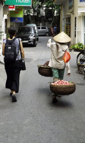 Vendor in old Hanoi, Vietnam walking beside a traveler