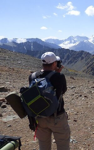 Goal Zero solar panel clipped to backpack while hiking off the grid in Kyrgyzstan, Central Asia